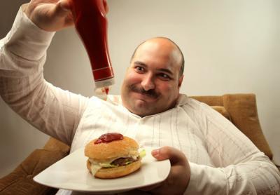 overweight-man-pouring-ketchup-on-a-hamburger.jpg