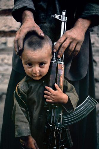AFGHN-10083_15-Un-bambino-accanto-a-suo-padre-AK-47-Kabul-Afghanistan-1992.jpg